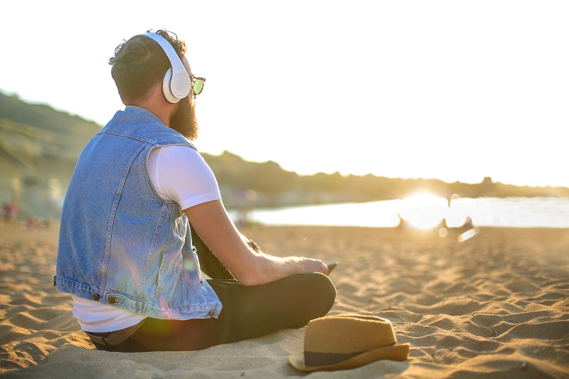 man listening to music while siting at the beach